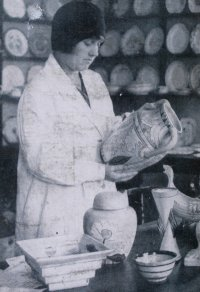 Photograph of Clarice Cliff examining the pattern on an 'Inspiration' vase